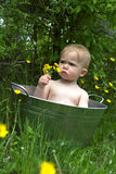 Nature Baby. Image of a cute baby sitting in a galvanized tub in a meadow Royalty Free Stock Photography