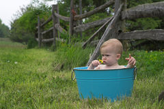 Nature Baby. Image of a cute baby sitting in a tub in a meadow Stock Photos