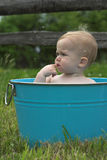 Nature Baby. Image of a cute baby sitting in a tub in a meadow, with dandelion seeds floating around his head Stock Photography