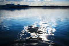 Abstract reflection of a cloud on a lake water surface. Nature background abstract reflection of a cloud on a lake water surface stock image