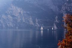 Nature background with achts on lake Garda Italy in sunny autumn day. Nature background with big and small yachts from yacht school sailing on lake Garda in Stock Images