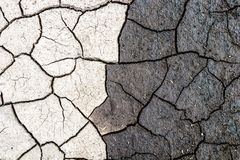 Nature background, border of dry and wet cracked mud. Concept of opposites, dark and light.  royalty free stock photos