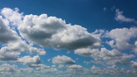 Time lapse clip of white fluffy clouds over blue sky. stock video footage
