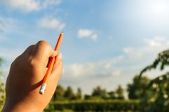 Pencil in left hand and blue sky. Nature background wooden pencil in left hand and blue sky royalty free stock photography