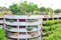 Nature and concrete. A building planted with trees to conserve a balance between nature and development Stock Photo