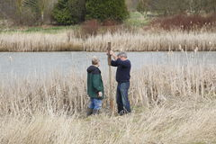 Nature Conservancy or Conservationists. Two men from Canada's Nature Conservancy erect man made nests for waterfowl Stock Image