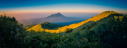 Nature covered by morning fog. Panoramic photo of mountains and Mount Merbabu covered with sunlight and fog during sunrise near Yogya in central Java province in Stock Photo