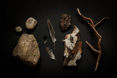 Nature details - stones, feathers, tree bark and branch on black Stock Image
