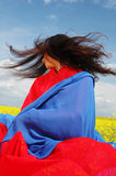 Nature drama 2. Girl in the meadows, asian-style dressed, live colours, hair in the wind