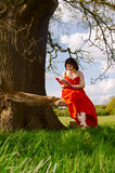 Nature and education. A young woman, in a traditional style dress, reading a book and surrounded by grass, sitting beside a tree on a sunny day Stock Photo