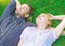 Nature fills them with freshness and peace. Man unshaven and girl lay on grass meadow. Guy and girl happy carefree enjoy royalty free stock images