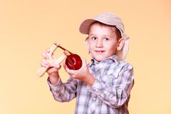 Young boy use sling shot shoot apple. Royalty Free Stock Images