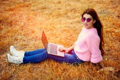 Nature and gadgets. A beautiful young woman is sitting on the grass in the coutryside with a laptop. Lifestyle, autumn fashion. Nature and gadgets royalty free stock photos