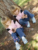 Nature Girls. Twin sisters play with pine cones on a warm spring day Royalty Free Stock Photo