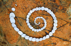 Nature Harmony. Spiral of pebbles on the sea boulder stock photos