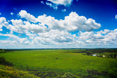 Nature landscape with green meadow, view from hill, bright blue sky with clouds Stock Photography
