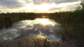 Nature landscape lake reflection of clouds in the water sunset sunlight stock footage