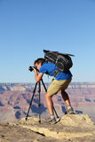 Nature landscape photographer in Grand Canyon. Taking picture photos with SLR camera and tripod during hike on south rim. Young man hiker enjoying landscape in Royalty Free Stock Photo