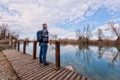 Hiker with backpack over wood pier on shore of river. Nature landscape. Senior hiker with backpack over the wood pier on shore of river Royalty Free Stock Image