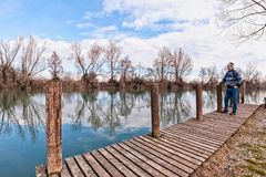 Hiker with backpack over wood pier on shore of river. Nature landscape. Senior hiker with backpack over the wood pier on shore of river Stock Image