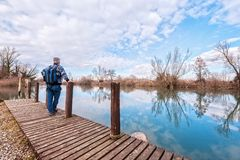 Hiker with backpack over wood pier on shore of river. Nature landscape. Senior hiker with backpack over the wood pier on shore of river Stock Images