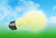 Nature Lightbulb. A yellow light bulb is in front of a nature background with a blue sky filled with clouds and a green base Royalty Free Stock Image
