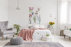Nature lover`s bright bedroom interior with a wall art of flowers and birds painted on a fabric above a bed which is dressed in g. Reen plants pattern on white royalty free stock photo