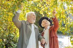 Positive elderly people standing under the tree royalty free stock photo