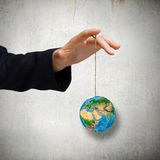 Nature and mankind. Close up of human hand holding Earth planet on rope. Elements of this image are furnished by NASA Royalty Free Stock Images