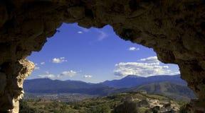 Nature mountains. Mountain view throught an antique stone wall stock image