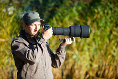 Nature photographer. Young nature photographer with taking photos using telephoto lens Stock Photo