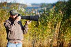 Nature photographer. Young nature photographer with taking photos using telephoto lens Stock Image