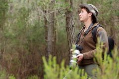 Nature Photographer. Photographer in nature taking pictures in forest. Outdoors man hiking with DSLR camera with tele lens looking to the side copy space. From Royalty Free Stock Image