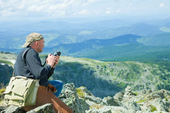 Nature photographer. Taking pictures outdoors during hiking trip on Altai mountains, Siberia Royalty Free Stock Photo