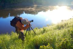 Nature photographer. Landscape photographer at work by the misty waters during  the sunrise Stock Photo