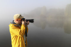 Nature photographer in action on fogy dawn Royalty Free Stock Photography