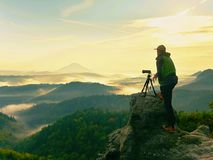 Nature photographer in the action.  Man silhouette above a misty clouds,. Morning hilly landscape Royalty Free Stock Photos