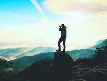 Nature photographer in the action.  Man silhouette above a misty clouds,. Morning hilly landscape Royalty Free Stock Photography