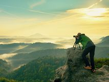 Nature photographer in the action.  Man silhouette above a misty clouds,. Morning hilly landscape Stock Images