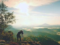Nature photographer in the action.  Man silhouette above a misty clouds,. Morning hilly landscape Stock Photo