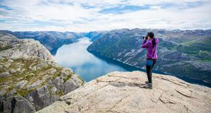 Nature photographer Beautiful Nature Norway Preikestolen or Prek. Nature photographer tourist with camera shoots while standing on top of the mountain. Beautiful Stock Image