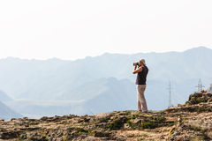 Nature photographer with camera on top mountain Royalty Free Stock Images