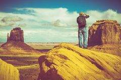 Nature Photographer. Caucasian Nature Photographer in Monuments Valley Arizona, United States. Photographer with Backpack Taking Nature Pictures Royalty Free Stock Photography