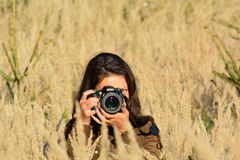 Nature photographer girl in yellow field Royalty Free Stock Photo