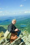 Nature photographer on mountain peak Royalty Free Stock Photo