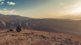 Nature photographer in mountains. At sunset Stock Images
