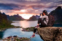 Nature photographer Norway Lofoten archipelago. Nature photographer tourist with camera shoots while standing on top of the mountain. Beautiful Nature Norway Royalty Free Stock Images