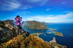 Nature photographer Norway Lofoten archipelago. Nature photographer tourist with camera shoots while standing on top of the mountain. Beautiful Nature Norway Royalty Free Stock Photography