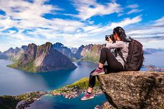Nature photographer Norway Lofoten archipelago. Nature photographer tourist with camera shoots while standing on top of the mountain. Beautiful Nature Norway Stock Photography