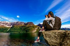 Nature photographer Norway Lofoten archipelago. Nature photographer tourist with camera shoots while standing on top of the mountain. Beautiful Nature Norway Royalty Free Stock Photo